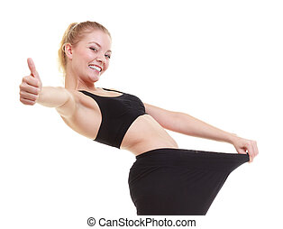 happy woman showing how much weight she lost, big pants -...