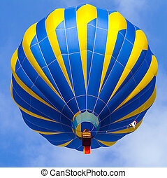 Hot Air Balloon in cloudy sky - Hot Air Balloon with blue...