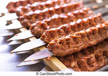 Seasoned Adana Kebabs on Skewers Waiting to be Cooked -...