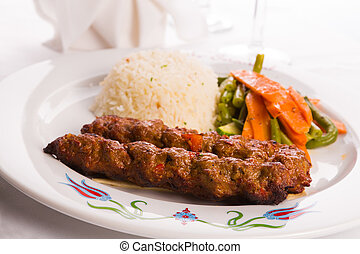 Turkish Adana Kebap with rice pilaf and vegetables served on...
