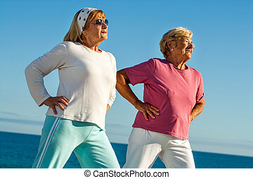 Elderly girls stretching outdoors - Portrait of two elderly...