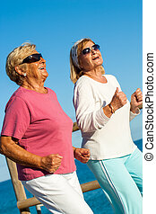 Happy senior ladies jogging together - Portrait of happy...