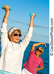 Senior woman lifting weights on beach - Senior woman doing...