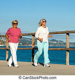 Senior women jogging together outdoors - Senior fitness...