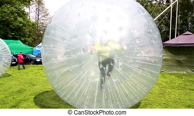 Lady playing inside human hamster ball kid inside a zorb ball