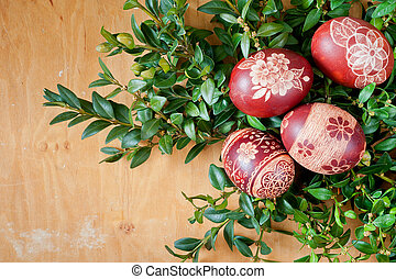 Easter eggs at green boxwood - Red scripts at wooden...