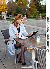 Business woman using tablet on lunch break. - Adult business...