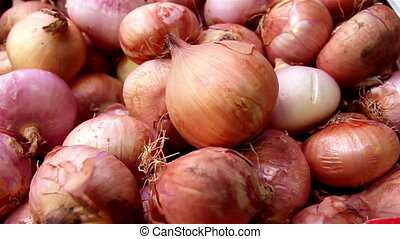 Piled red onions bulbs in a box