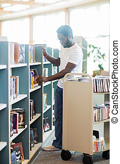 Librarian Arranging Books In Shelf At Library - Full length...