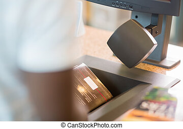 Librarian Scanning Books At Library Counter