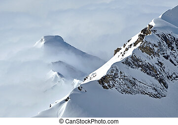 View of snow capped peaks above clouds