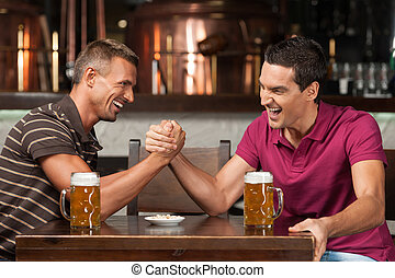 Having fun at the bar Two friends drinking beer and having...