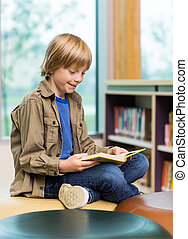 Happy Boy Reading Book In Library - Happy young boy reading...