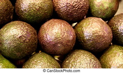 Several brown chicos set of avocadoes are piled - Several...