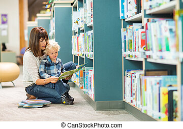 Teacher And Boy Reading Book By Bookshelf - Full length of...
