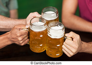 Cheers! Close-up of three hands holding beer mugs