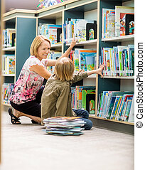 Female Teacher And Boy Selecting Books In Library - Happy...