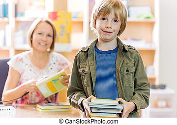 Boy Checking Out Books From Library - Portrait of happy...