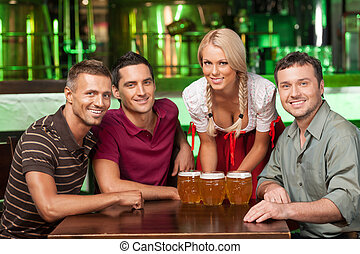 Friend at the beer festival. Three cheerful male friends and waitress in traditional German costume looking at camera and smiling