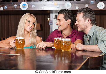 Flirting at the bar. Two cheerful young men and beautiful young women talking at the bar and drinking beer