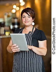 Beautiful Owner Holding Digital Tablet In Cafeteria -...