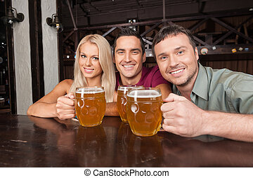 Friends at the bar. Two cheerful young men and beautiful young women looking at camera and smiling while holding glasses with beer