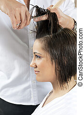 hair salon - portrait of young woman having her hair being...