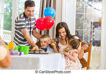 Family Eating Cupcakes At Birthday Party - Happy parents and...