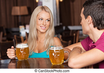 Beer lovers. Young cheerful couple drinking beer at the bar
