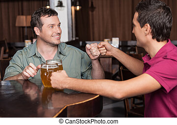 Friends forever. Two friends drinking beer at the bar