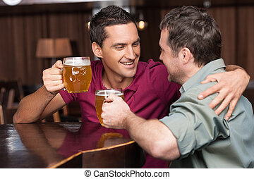Friends in beer pub. Two cheerful friends drinking beer and...