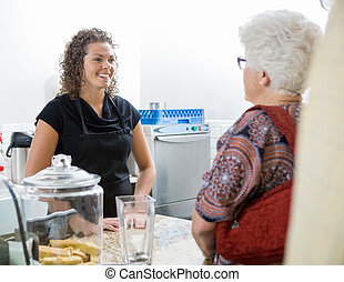 Cafe Owner Attending Senior Woman - Smiling female cafe...