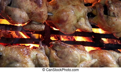 Juicy whole roasted chickens on flames
