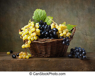 Still life with grapes in a basket on the table