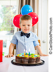 Boy Licking Lips While Looking At Birthday Cake