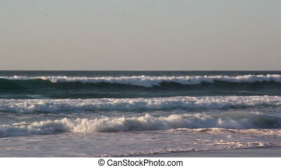 Series of waves rushing to the shoreline seawater sport...
