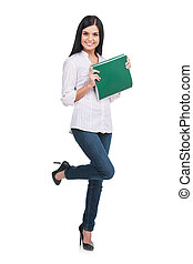 Confident woman. Full length of cheerful young woman holding note pad in her hands and smiling while standing isolated on white