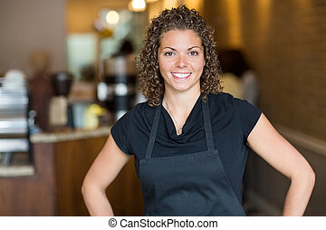 Happy Waitress Standing In Cafe - Portrait of happy mid...