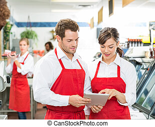 Butchers Using Digital Tablet At Store - Male and female...