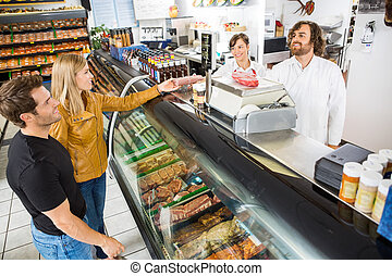 Couple Purchasing Meat From Salesman In Shop - Couple...