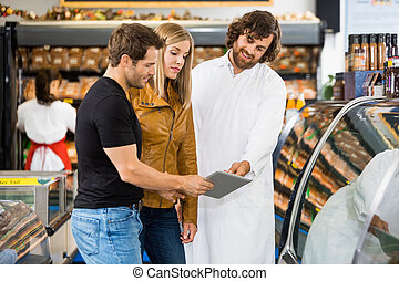 Salesman And Couple Using Digital Tablet At Butcher's Shop
