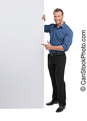 Happy man. Full length of cheerful young man standing near the poster and pointing it while isolated on white