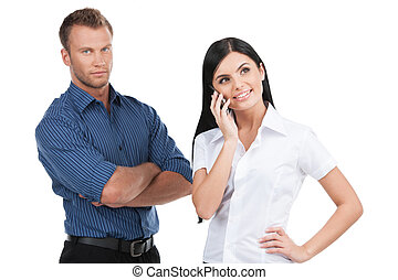 Business people. Young man and woman standing close to each other while woman talking on the mobile phone