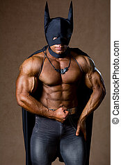A muscular man in a Batman costume. Hero athlete with strong...
