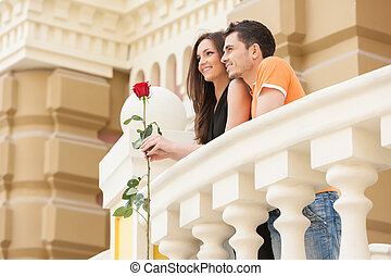 Loving couple. Low angle view of cheerful young couple standing close to each other and looking away
