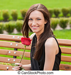 Girl with flower. Beautiful young woman holding red rose and...