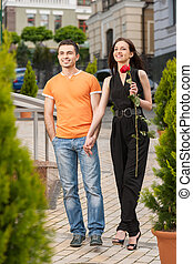 Happy loving couple. Full length of cheerful young couple holding hands and looking away
