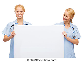smiling female doctor or nurse with blank board -...