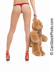 Woman with toy bear. Rear view of young women in red panties...