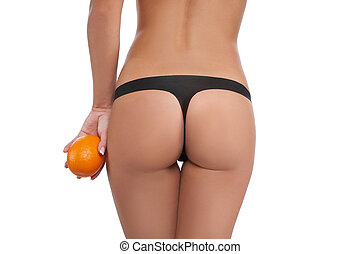 Skin care Rear view of woman holding orange near her...